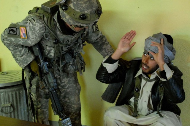 A Soldier interrogates a suspected insurgent during a role play.
