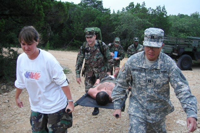 """Ms. Julie Sullivan, Maj. Brett Weldon and Capt. Ernesto Raymundo carry a human patient simulator on a litter during a trauma field training exercise at Camp Bullis. During an FTX, students use skills and equipment introduced in the classroom to include triage, airway management, IV access and chest tube placement. """"Simulation training is an important bridge between didactic knowledge and clinical experience,"""" said Lt. Col. Thomas Ceremuga, anesthesia nursing program director."""