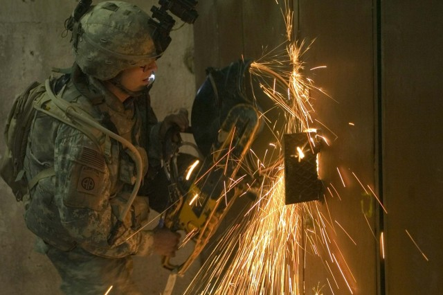 Cpl. Benjamin Meyer of Steven's Point, Wis., a combat engineer with Company A, 325th Special Troops Battalion, 2nd Brigade Combat Team, 82nd Airborne Division, uses a power saw to cut away storefront locks during an early morning raid on suspected sniper positions in Baghdad's Adhamiyah district.