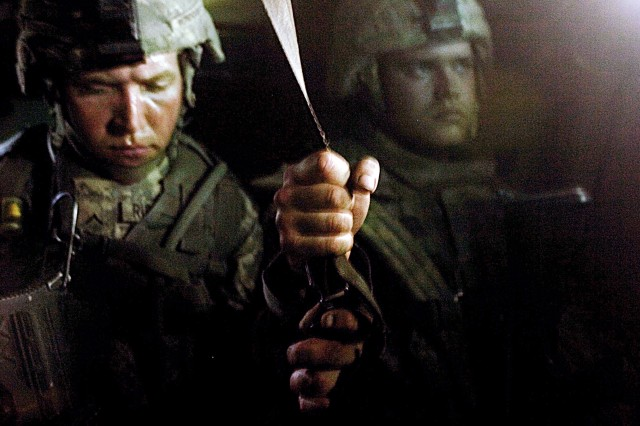 Pvt. Eric Rundquist, left, and Pvt. Jason Taylor, both with 1st Platoon, Company B, 1-12 Combined Arms Battalion, 3rd Brigade Combat Team, 1st Cavalry Division, hold on to a strap inside a Bradley fighting vehicle after the Bradley hit a roadside bomb. The Soldiers were en route to the Forward Operating Base Gabe medical station after one of their fellow Soldiers was injured when they encountered sporadic sniper fire for about two hours during a house-clearing mission in the Tahrir neighborhood of Baqubah.