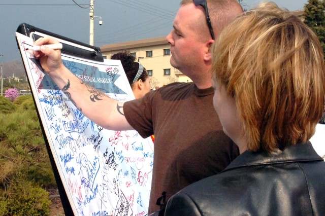 """An off-duty Soldier shows his support against sexual assault by signing the """"Sexual Assault Prevention Board"""" during a sexual assault awareness rally held at Camp Casey April 7."""