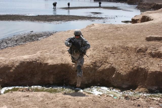 1st Lt. Brain Casey jumps across a stream in the Fadaliyah neighborhood.
