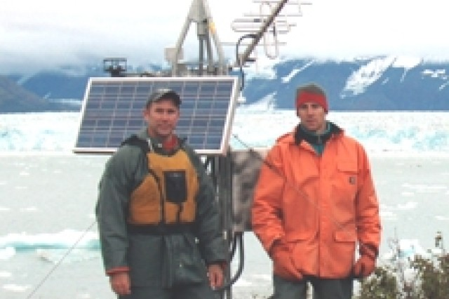 Mr. Dan Stenstream (left) and Mr. Greg Hanlon stand in front of the climate station/satellite repeater on Haenke Island.