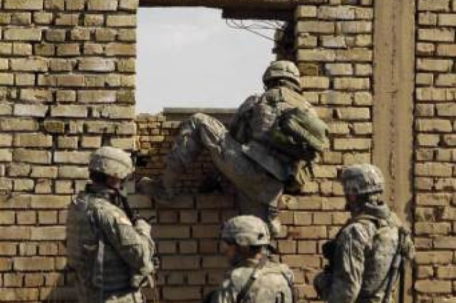 Soldiers climb through a wall to get to their next objective.