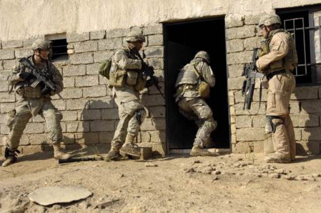 Soldiers cautiously enter a house.