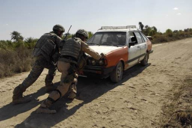 Sgt. Michale Holeman and 1st Sgt. John Coomer assist an Iraqi civilian who is trying to start his vehicle.