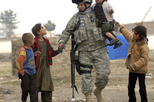 Sgt. 1st Class Ed Franco plays with local refugee children in Dar Ul Aman, Kabul, Afghanistan, April 8, during a volunteer community outreach program. He and fellow Soldiers from the 10th Mountain Division are distributing clothes, shoes and toys donated by U.S. citizens.