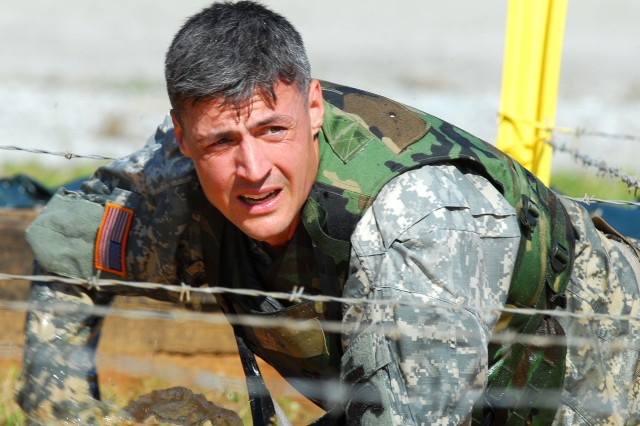 FORT BENNING, GA -- April 20, 2007 -- Sgt. 1st Class Adam Nash, 75th Ranger Regiment, crawls through a mud-filled pit under barbed wire during the first day of the 2007 Lt. Gen. David E. Grange Best Ranger Competition.  Nash, a native of Hyannis, Mass., won the competition in 2004 and is partnered with Sgt. 1st Class Billy Pouliot. The three-day continuous competition will take the competitors over 60 miles by foot carrying backpacks weighing nearly 85 lbs.