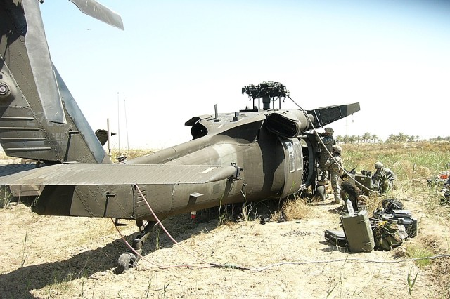 Soldiers from the 1st Air Cavalry Brigade's Downed Aircraft Recovery Team (DART) prepare a Black Hawk helicopter for a recovery mission April 5. The helicopter made a forced landing southeast of Baghdad, and the DART team deployed to the site to assess the damage and take the aircraft back to Camp Taji.