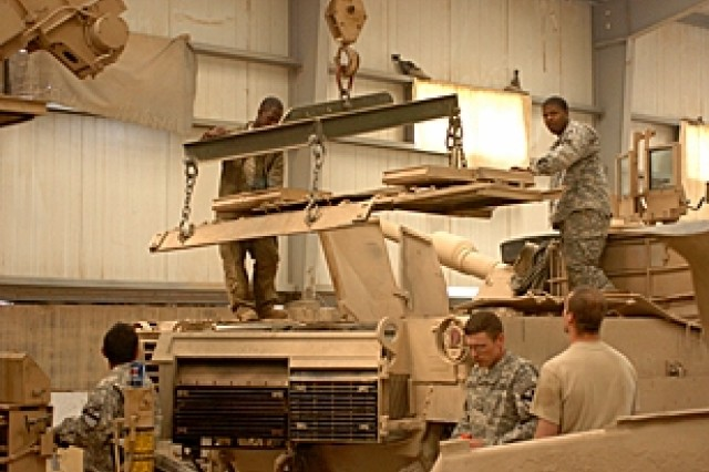 Tank mechanics and operators guide the back cover down onto a tank in the mechanics bay at Forward Operating Base Brassfield-Mora near Samarra, Iraq.