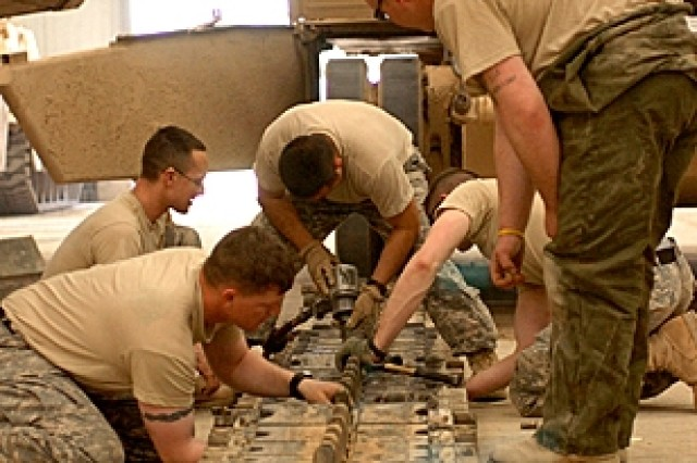 Tank mechanics and operators from Company D, 3rd Battalion, 8th Cavalry Regiment, replace a track on a tank in the mechanics bay at Forward Operating Base Brassfield-Mora near Samarra, Iraq.