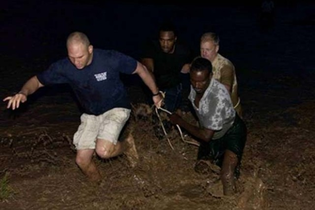 (Clockwise from left) Sgt. Rovell Thomas, Delta Company, 1st Battalion, 3rd U.S. Infantry Regiment; Senior Airman Travis Manning, Combined Joint Task Force-Horn of Africa Combat Camera; Col. Vic Adamson, 350th Civil Affairs Command Functional; Specialty and a Djiboutian volunteer cross a raging river to rescue an injured teenager.