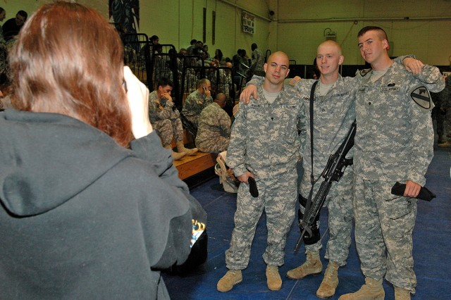 Christine Minteer takes a picture of Spc. Phillip Knorr, her husband, Pfc. Harry Minteer, and Spc. Cameron Riggins, who are construction equipment operators with Company E, 2nd Battalion, 8th Cavalry Regiment, 1st Brigade Combat Team, 1st Cavalry Division. Minteer and approximately 100 more Soldiers from the First Team deployed to Iraq April 20, after saying their final farewells to friends and family at the Kieschnick Physical Fitness Center at Fort Hood, Texas.