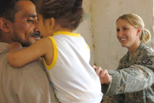 Pfc. Lisa Dueke, a medic from the 15th Field Artillery Regiment, 10th Mountain Division, interacts with an Iraqi patient during a medical mission in Mamadiyah, Iraq, April 12.