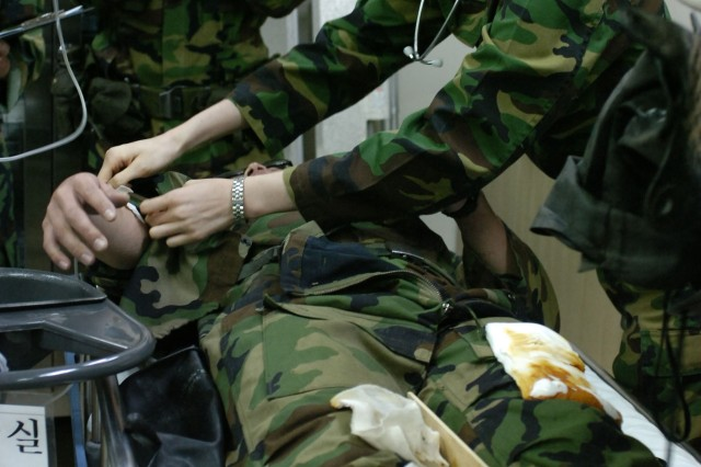 A South Korean army nurse examines a U.S. Soldier for simulated combat wounds as a South Korean army public affairs Soldier videotapes the procedure March 28, at the Armed Forces Hospital in Yang Ju, South Korea. The hospital staff is participating in a combined medical evacuation scenario that is part of Exercise Foal Eagle 2007.