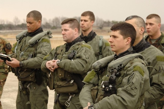 AH-64 Apache attack helicopter pilots and aircrew listen to a safety brief prior to a training mission in South Korea.