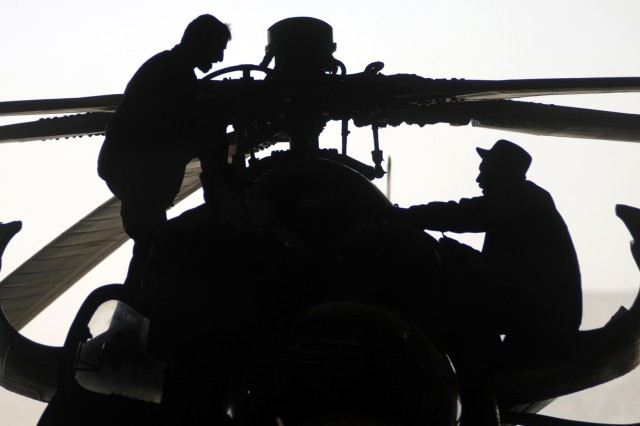 Afghan National Air Corps maintainers repair an MI-35 Hind helicopter at the Kabul International Airport flightline in Afghanistan.