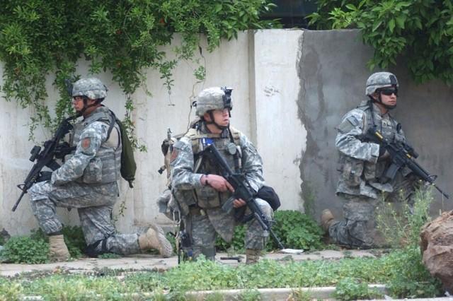 Soldiers halt but remain vigilant during the patrol.