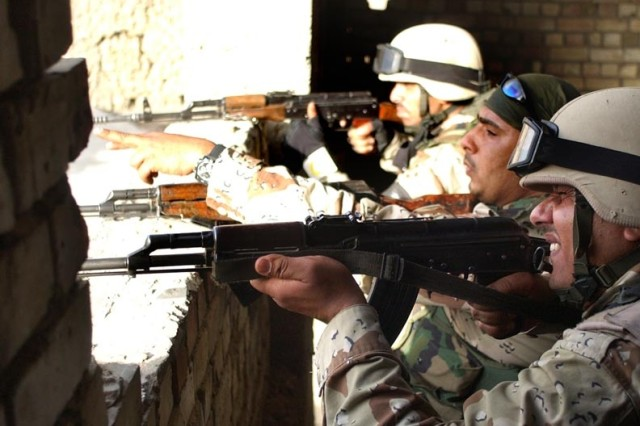 Iraqi Soldiers react during a firefight with insurgents.