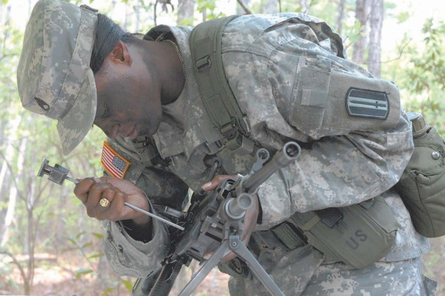 Staff Sgt. Alanna Payne, drill sergeant, Company F, 3rd Battalion, 60th Infantry Regiment, uses a cleaning rod  to unlatch the hook of the hinge pin latch of an M-60 machine gun as part of disassembling the weapon during Tuesday's Drill Sergeant of the Year competition.