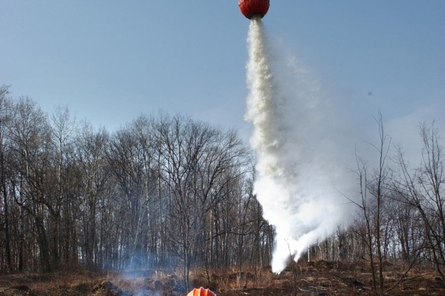 Mr. Mike Eilers guides a UH-60A Black Hawk helicopter crew from the Minnesota National Guard as it dumps water on a small controlled fire during training at Camp Ripley, Minn., April 20. Mr. Eilers is with the Forestry Division of the Minnesota Department of Natural Resources.
