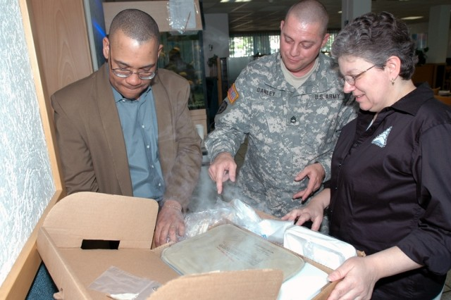Department of Defense Combat Feeding program integrator Kathy-Lynn Evangelos (right) shows off the contents of the  Unitized Group Ration-Express to Heidelberg Garrison food service officer Christopher B. Jenkins and Sgt. 1st Class Mark Danley, V Corps' senior food service sergeant, April 27, 2007.