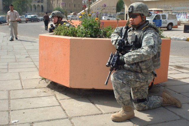 Soldiers monitor vehicular traffic for suspicious activity.
