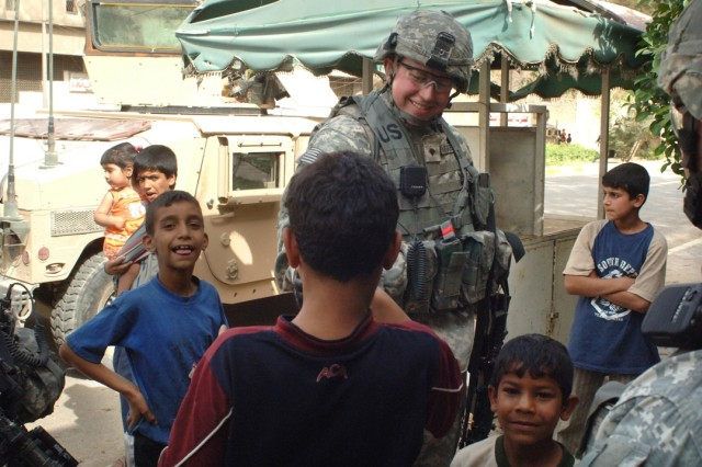 A Soldier hands out candy to Iraqi children.