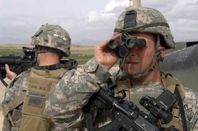 Sgt. Joseph Evans scans the area for Taliban and other extremists while Spc. Brendon Quisenberry pulls rear security during a halt.