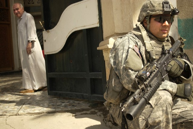 Sgt. Luis Cruise pulls security outside a house during a combined cordon and search mission with the Iraqi Army in Ameriyah, April 25. Sgt. Cruise is with the 3rd Stryker Brigade Combat Team, 2nd Infantry Division.