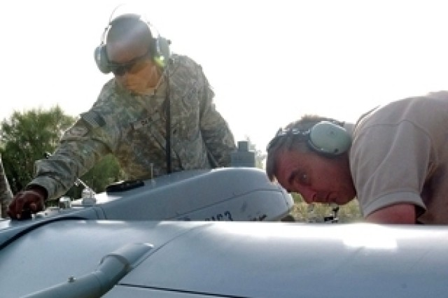 Spcs. Brian Davis and Jerry Kelley perform maintenance on a Shadow unmanned aerial vehicle, April 27, 2007, at Jalalabad Airfield.