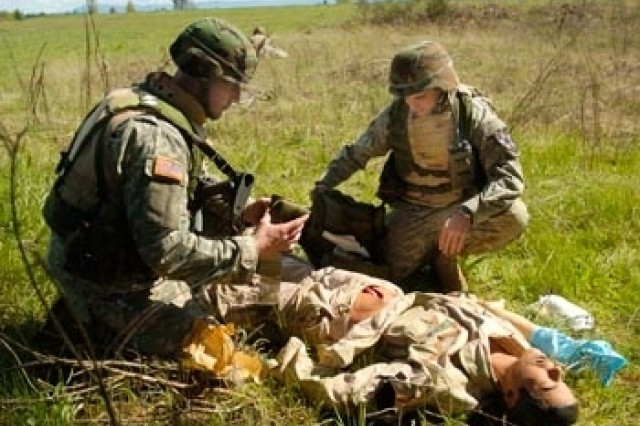 Staff Sgt. Christopher Rentzel, left, and Pfc. Zachary Purrington, both from 2-1 Inf., perform first aid on a simulated casualty near Range 59.