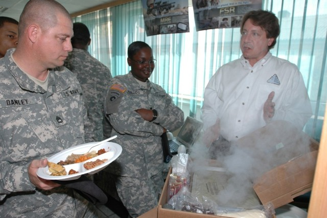 Gerald Darsch, director of Department of Defense combat feeding, demonstrates the Unitized Group Ration-Express to Sgt. 1st Class Mark Danley and Spec. Tina Avalos during MRE field tests held in Heidelburg, Germany.