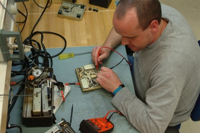 """Kevin Berry, electronics mechanic, troubleshoots a 1A2 module for the AN/ARN-89 Direction Finder Set used in aircraft such as the Apache, Black hawk and """"Huey"""" helicopters. Berry works in the Avionics Division. (Photo by Tony Medici)"""