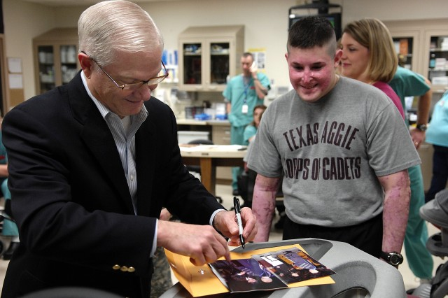 Defense Secretary Robert M. Gates signs a graduation photo for Texas A&M University graduate Marine 1st Lt. Dan Moran during a tour of the burn rehabilitation center at Brooke Army Medical Center.
