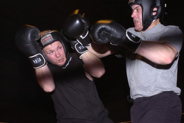 """Sgt. Charles Crawford (left) with Company C, 5th Battalion, 20th Infantry Regiment, tries to avoid a punch from Sgt. Chad Wright with Headquarters and Headquarters Troop, 1st Squadron, 14th Cavalry Regiment, during the """"Black Jack Boxing Fight Night Tournament"""" May 5. Soldiers from throughout the 2nd """"Black Jack"""" Brigade Combat Team, 1st Cavalry Division, are participating in the two-weekend event at Forward Operating Base Union III in central Baghdad."""