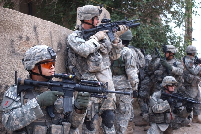 Staff Sgt. John Gregory (left) and fellow Soldiers take cover during a dismounted patrol in the Adhamiya district of Baghdad, April 10. The Soldiers are from Company C, 1st Battalion, 26th Infantry Regiment, 1st Infantry Division.