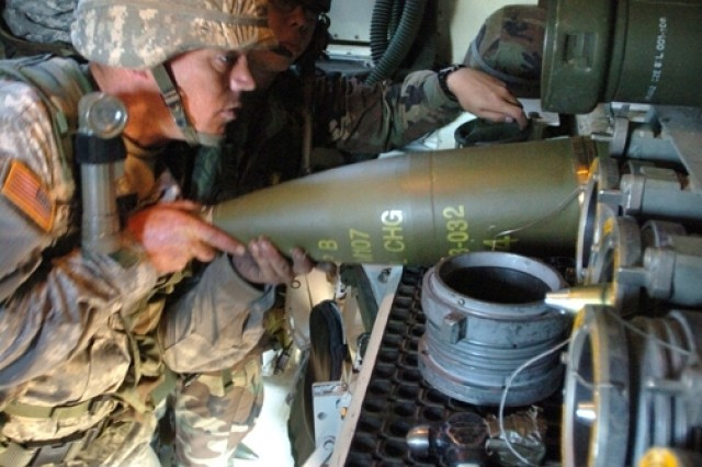 Pvt. Mitchell Starnes and Sgt. Casey Xiong load ammunition inside a Paladin.