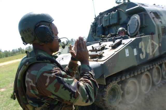 Staff Sgt. Anthony Allen directs the vehicle.
