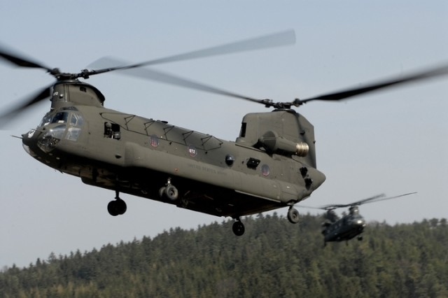 CH-47 Chinook helicopters from the 12th Combat Aviation Battalion drop into a landing zone to pick up the paratroopers.
