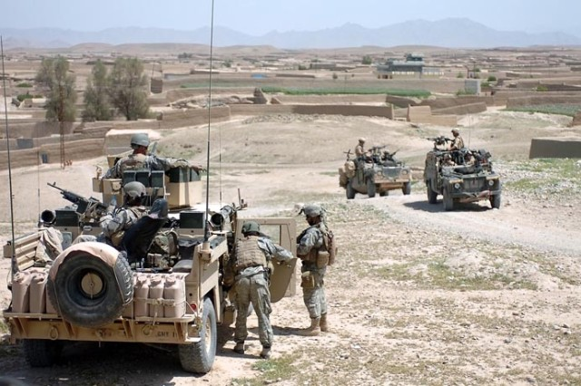 American and British Soldiers make a security halt during a combat patrol in Sangin District.