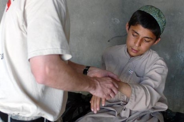 A Special Operations physical therapist examines an Afghan child's wrist during a medical relief mission in Sangin City.
