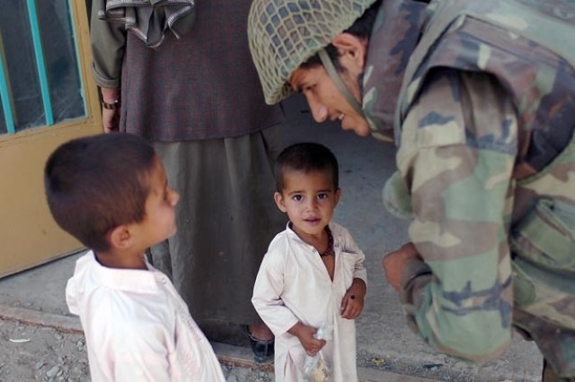 Not all of the work is fighting. A 1st Kandak, 209th Afghan National Army Corps Soldier greets two children who came to a scheduled medical civil assistance program relief mission at Sangin City. Afghan and coalition forces treated more than 500 adults and children during a 3-day period.