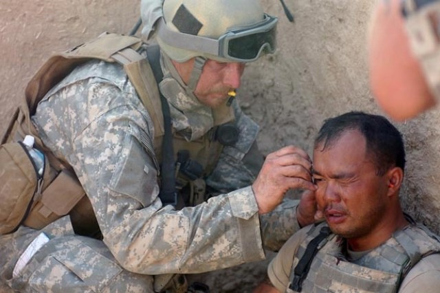 A Special Forces medic treats another Soldier who received shrapnel wounds from a rocket-propelled grenade explosion while battling Taliban fighters. The Soldier was able to continue fighting minutes later.
