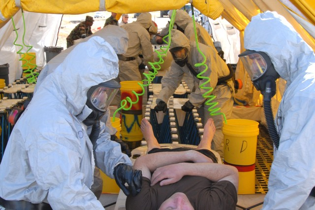 Spcs. Lan Borba and Marshall Boyett complete a final contamination check on a mock victim.