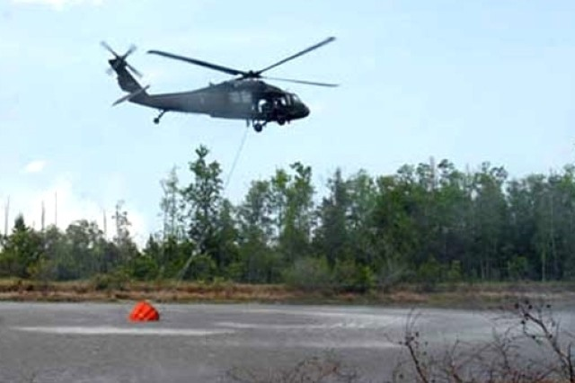 A UH-60 Black Hawk helicopter from the Florida National Guard fills its 700-gallon bucket from a pond to dump on wildfires burning in Flagler and Volusia counties in Florida.