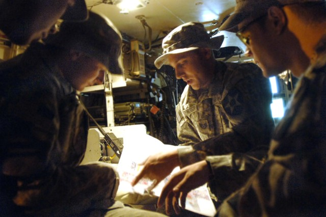 During an early morning planning session in the back of a Stryker assault vehicle, Staff Sgt. Christopher Froboccino (center) shows his Soldier counterparts the route they will be traveling through Baghdad. Sergeant Froboccino is a joint terminal attack controller in charge of communicating coordinates for close-air support during fire fights with enemy ground forces.