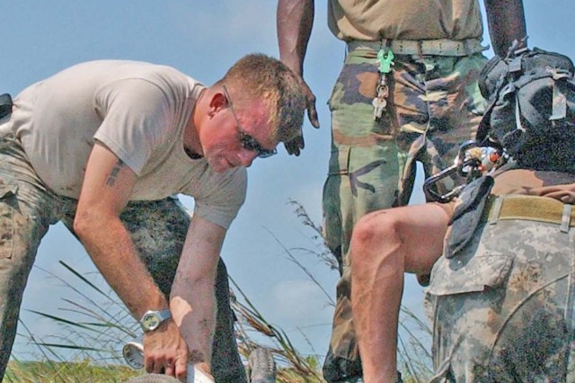 Sgt. Michael Linn, a Black Hawk crew chief, tightens one of the slingload straps.