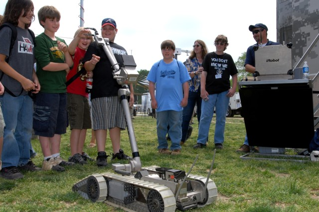 Young visitors interact with an IRobot on while Ray Howard, far right, controls the device using a remote control similar to that of a video game joystick during National Public Service Recognition Week, May 10, 2007, on the National Mall in Washington, D.C.
