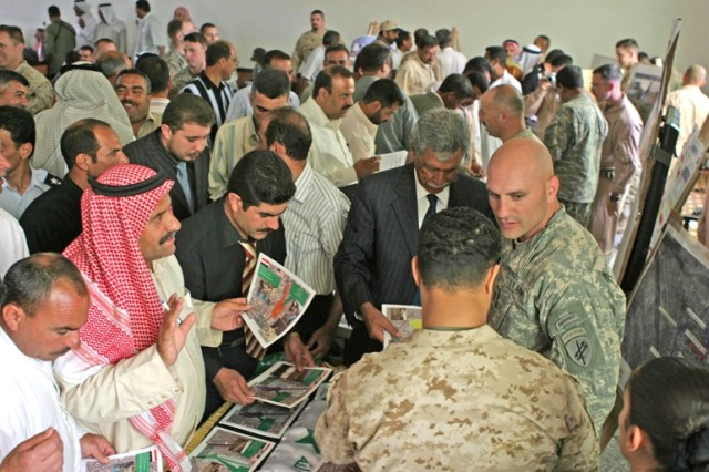 Iraqi contractors gather around display tables to look at and sign up for reconstruction projects for the Ramadi area during the Ramadi Reconstruction Conference, April 22.
